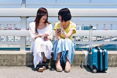 スマホを見ながら会話する女性の素材 [FYI00603630]