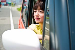 車の運転席から外を見る女性の素材 [FYI00603647]