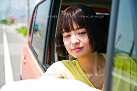 車の窓から顔を出す女性の素材 [FYI00603651]