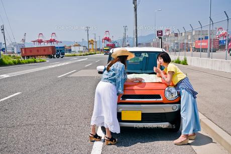 ボンネットの上で地図を広げる女性二人の素材 [FYI00603653]