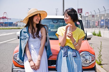 車の前で会話する女性二人の写真素材 [FYI00603659]