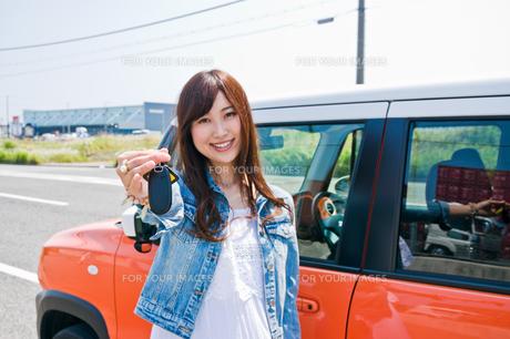 車の前で鍵を見せる女性の素材 [FYI00603661]