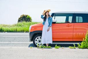 車の前で笑顔で立つ女性の素材 [FYI00603662]