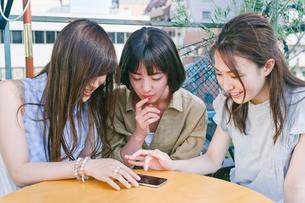 スマホを見ながら会話する女性三人の素材 [FYI00603719]