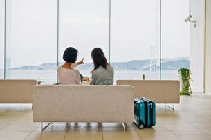ソファーに座り海を指差す女性の素材 [FYI00603723]