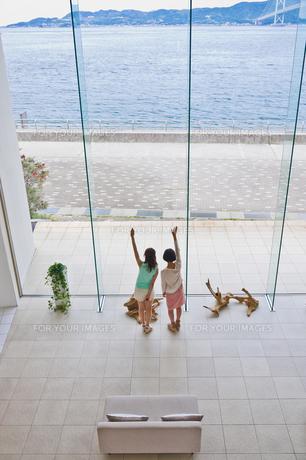 海に向かって手を振る女性の素材 [FYI00603730]