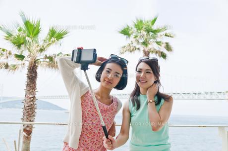 海をバックに自撮りする女性の写真素材 [FYI00603741]