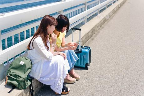 スマホを見ながら会話する女性の写真素材 [FYI00603749]