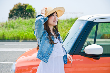 車の前で笑顔で立つ女性の素材 [FYI00603752]