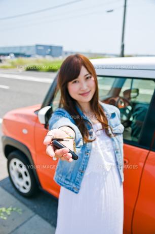 車の前で鍵を見せる女性の写真素材 [FYI00603753]