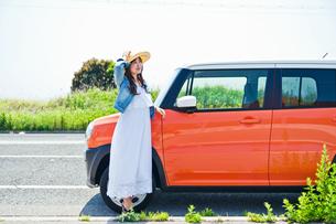 車の前で笑顔で立つ女性の素材 [FYI00603754]