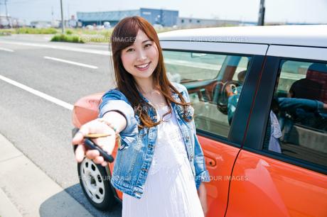 車の前で鍵を見せる女性の素材 [FYI00603755]