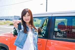 車の前で鍵を見せる女性の素材 [FYI00603756]