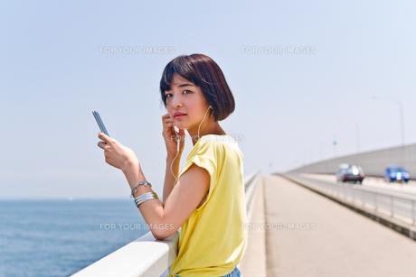 橋の上で音楽を聴く女性の素材 [FYI00603782]