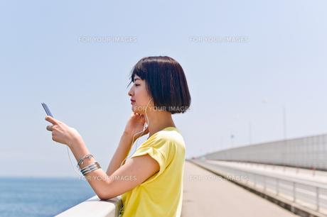 橋の上で音楽を聴く女性の素材 [FYI00603783]
