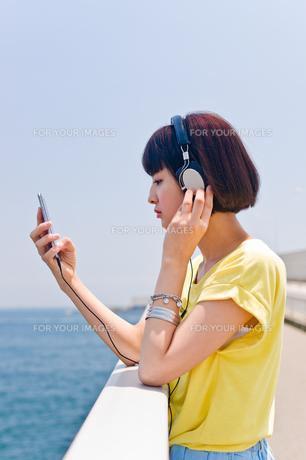 スマホで音楽を聴く女性の素材 [FYI00603791]