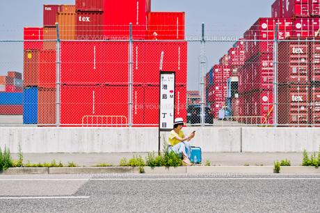 スマホを見ながらバス停でバスを待つ女性の素材 [FYI00603802]