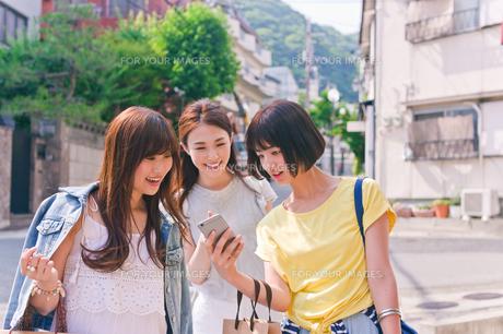 スマホでお店を探す女性三人の素材 [FYI00603824]
