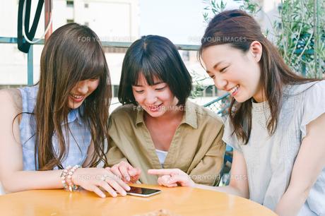 スマホを見ながら会話する女性三人の素材 [FYI00603843]