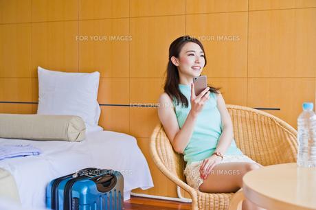 ホテルでスマホを持つ女性の写真素材 [FYI00603854]