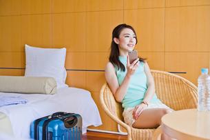 ホテルでスマホを持つ女性の素材 [FYI00603854]