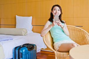ホテルでスマホを持つ女性の素材 [FYI00603856]