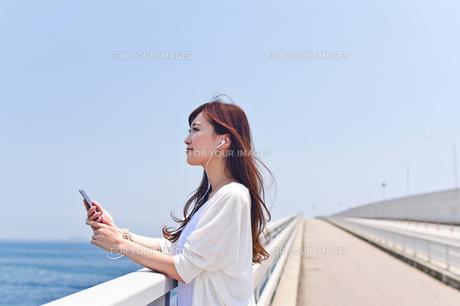 橋の上で音楽を聴く女性の素材 [FYI00603864]