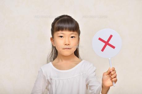 バツのプレートを出す女の子の写真素材 [FYI00604927]