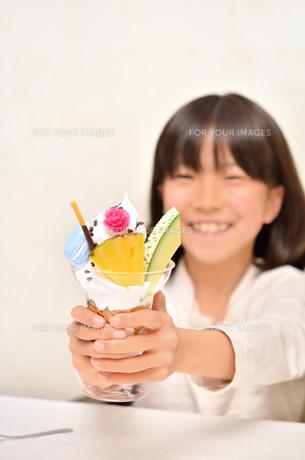 パフェを差し出す女の子(パフェにフォーカス)の写真素材 [FYI00613903]