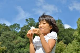 おにぎりを食べる女の子(青空)の写真素材 [FYI00618289]