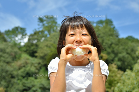 おにぎりを食べる女の子(青空)の写真素材 [FYI00618290]