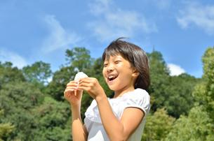 おにぎりを食べる女の子(青空)の写真素材 [FYI00618293]