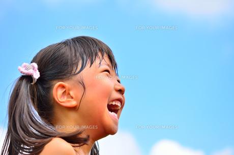 青空で笑う女の子の写真素材 [FYI00618401]