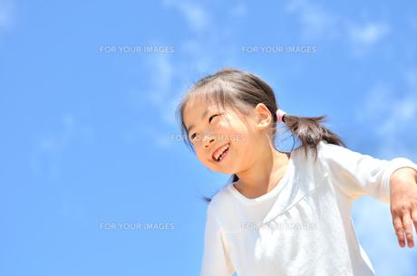 青空で笑う女の子の写真素材 [FYI00618415]