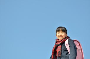 青空で笑う小学生の女の子の写真素材 [FYI00618581]