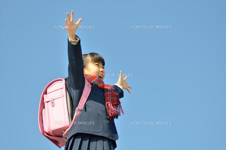 青空で手を広げる小学生の女の子の写真素材 [FYI00618585]