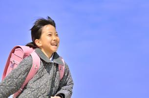 青空で走る小学生の女の子(ランドセル)の写真素材 [FYI00620727]