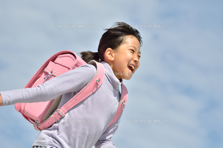 青空で走る小学生の女の子(ランドセル)の写真素材 [FYI00620728]