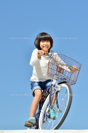 青空で自転車に乗る女の子の写真素材 [FYI00620765]