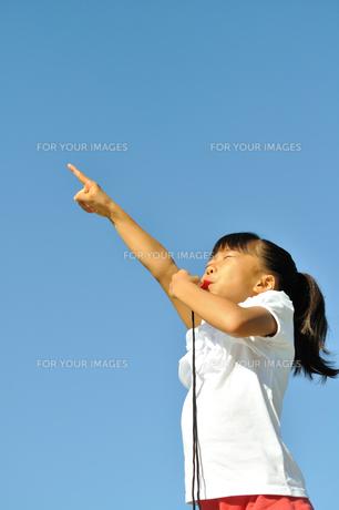 青空で笛を吹く女の子の写真素材 [FYI00620884]
