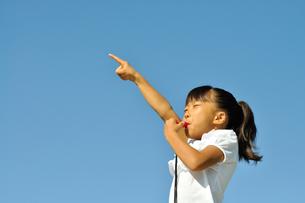 青空で笛を吹く女の子の写真素材 [FYI00620886]