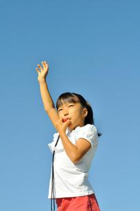 青空で笛を吹く女の子の写真素材 [FYI00620895]