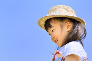 青空で笑う女の子(麦わら帽子)の写真素材 [FYI00621094]