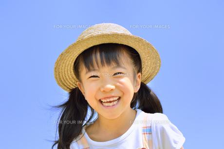 青空で笑う女の子(麦わら帽子)の写真素材 [FYI00621095]