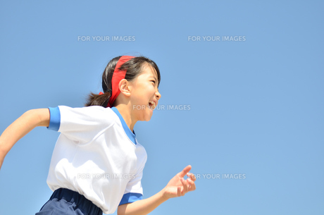 青空で走る小学生の女の子(体操服、運動会)の写真素材 [FYI00621142]