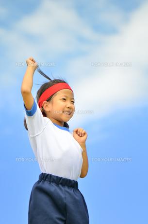 青空でガッツポーズをきめる小学生の女の子(運動会、体操服)の写真素材 [FYI00621272]