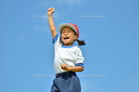 青空でガッツポーズをきめる小学生の女の子(運動会、体操服)の写真素材 [FYI00621275]
