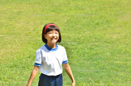 芝生広場で笑う小学生の女の子(運動会、体操服)の写真素材 [FYI00621291]