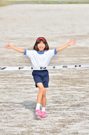 運動会で走る小学生女の子(ゴールテープ)の写真素材 [FYI00621340]