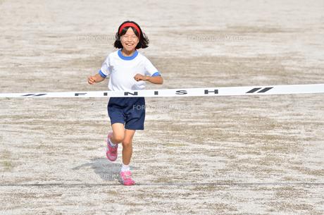 運動会で走る小学生女の子(ゴールテープ)の写真素材 [FYI00621346]